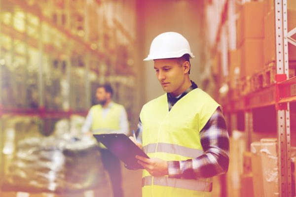 man-with-clipboard-in-safety-vest-at-warehouse-PK4JP5P